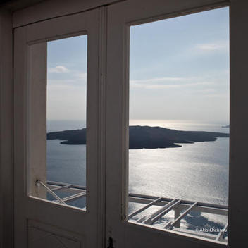 Blue sea and Santorini volcano from inside a balcony door.