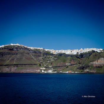 Fira city, Firostefani and Gialos port as seen from the ferry to Santorini.