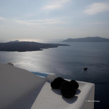 Volcano and Thirasia as seen from the Caldera in Fira, noon time