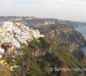 A panoramic photo of Fira, taken from Firostefani. The sun is going down.